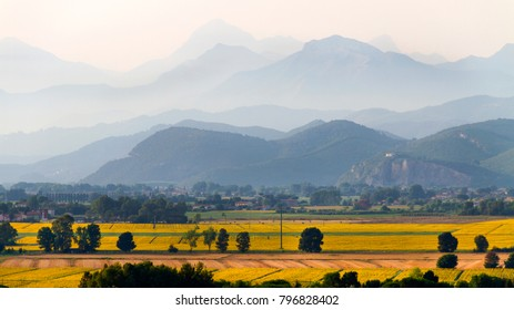 Idyllic and scenic countryside landscape - fields, forest, hills and mountains in the distance - Pisa, Tuscany, Italy; tourism, travel, vacation; background.