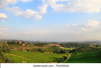 Idyllic and scenic countryside landscape - vineyards, orchard, fields, forest, hills and sky with clouds - Tuscany, Italy; tourism, travel, vacation; background.