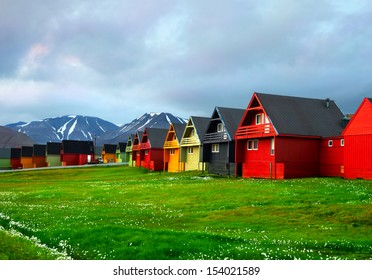 Idyllic scenic view, colorful houses and green field with arctic flowers against the background of dramatic sky and barren mountain in Longyearbyen, Spitsbergen archipelago (Svalbard), Norway, Europe
