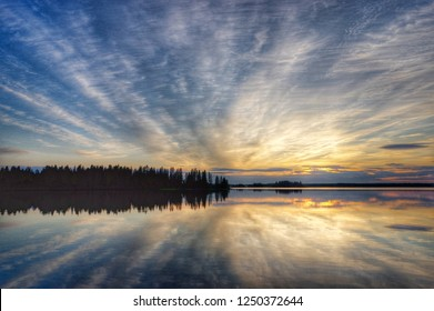 Idyllic seascape scenery with sea, trees and sky in sunset by the coast of north Sweden. Heavenly sky reflected like a mirror in totally calm water. A paradise on earth.