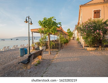 idyllic seaside promenade, morning scenery with bench, at Moscenicka Draga village, croatia. mediterranean house and oleander bush.