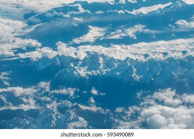 Idyllic snowy mountain peaks or tops under soft white clouds on grey rocky highland environment background. Overcast view from plane flight