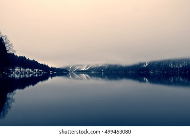 Idyllic snowy winter landscape on the lake with trees reflecting on the still water surface. Monochrome image filtered in nostalgic, retro, vintage style with soft focus, red filter and some noise.
