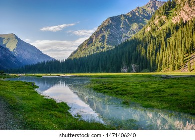 Idyllic summer landscape with hiking trail in the mountains with beautiful fresh green mountain pastures, river with reflection and forest. Terskey Alatoo mountains, Tian-Shan, Karakol, Kyrgyzstan