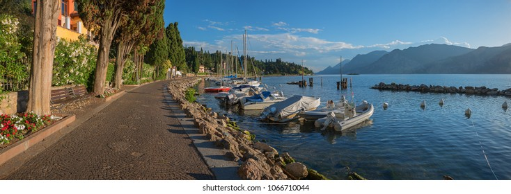 idyllic sunny lakeside promenade malcesine with moored colorful sailboats and mediterranean shore