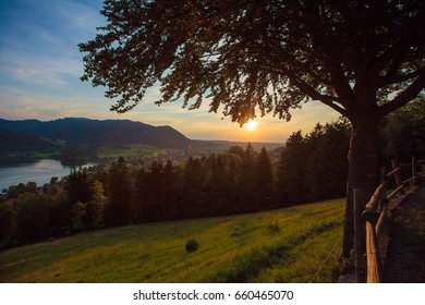 Idyllic sunset mountain landscape in the Alps with lake, green meadows and mountains