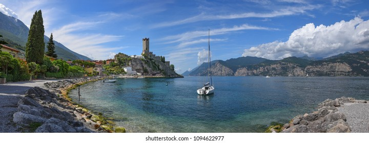idyllic tourist destination malcesine. lakeside promenade with bathing beach and view to scaliger castle. garda lake italy.