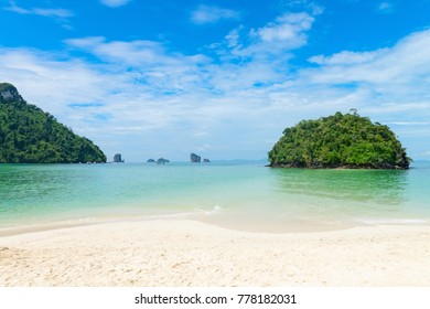 Idyllic tropical beach with clean white sand and green island on front. Tup Island Krabi, Thailand on a hot tropical  summer day.
