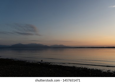 Idyllic view of beautiful Chiemsee lake with mountains on background during sunset