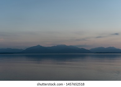 Idyllic view of Chiemsee lake with high mountains on background during sunset in dusk, Germany