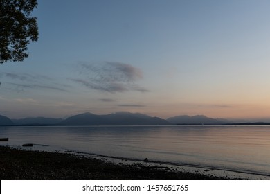 Idyllic view of Chiemsee lake with mountains on background during sunset in dusk