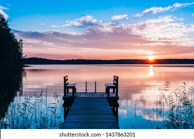 Idyllic view of the long pier with wooden bench on the lake in Finland. Sunset or sunrise over the water.