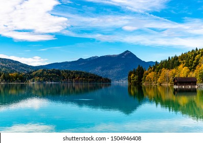 Idyllic view on Walchensee, lake Walchen with alps mountains. Bayern, Bavaria. Germany, border with austria, Tyrol , in autumn. Blue sky, clouds, colorful trees