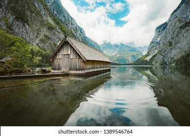 Idyllic view of traditional old wooden boat house at scenic Lake Obersee on a beautiful sunny day with blue sky and clouds in summer, Nationalpark Berchtesgadener Land, Bavaria, Germany