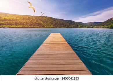 Idyllic view of the wooden pier in the lake with mountain scenery background. Wooden bridge on the lake. Long pier on lake and blue sky in summer.  Seagulls over pier.