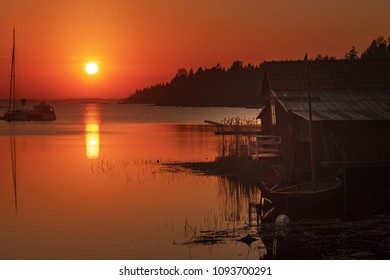 Idyllic warm orange sunset with dark silhouettes of the shore and and old boathouse with a modern marina and sailboats moored for the evening.