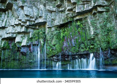Idyllic waterfall with turquoise blue lagoon and basalt columnar jointing rocks and cliffs surrounded it. Japanese landscape off the beaten track at Ogawa falls, Kagoshima, Kyushu, Japan