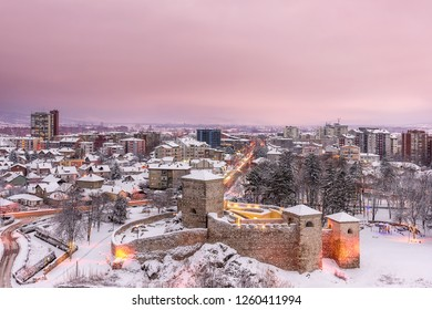 Idyllic winter cityscape, city lights, car trails and Christmas lights under a purple sunset sky and lighten ancient fortress