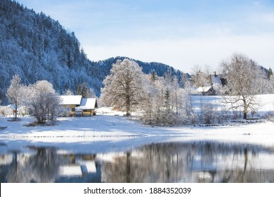 Idyllic winter landscape: Reflection lake, house and snowy trees and mountains