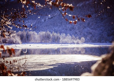 Idyllic winter landscape: Reflection lake, snowy trees and mountains