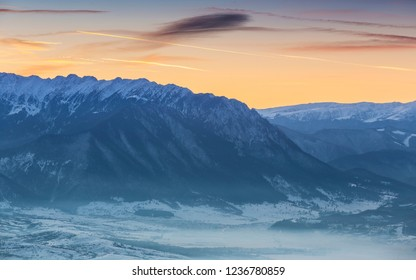 Idyllic winter landscape with snowy Piatra Craiului mountain range and misty valleys at sunset, Romania.