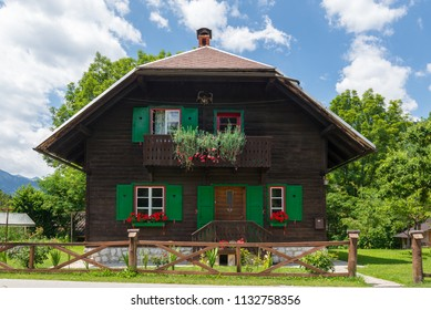 Idyllic wooden house with green wooden shutters and flowers in Bohinj, Slovenia