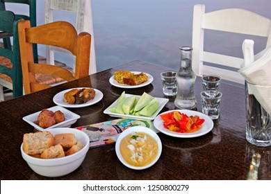 "IERAPETRA, CRETE ISLAND, GREECE - August 12, 2015. Table with traditional Cretan food (""mezze"") and raki, the traditional Cretan drink at a tavern (called ""Stsi Koumbares"")."