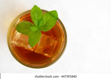 iew from above on ice tea,ice cubes,mint on ice on white background