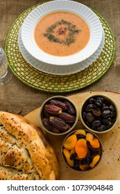 Iftar meal (time to break the fast) with sweet dry dates,apricot,black olives,soup,water and Ramadan bread.Beginning meal before main menu.Close up taken,isolated.
