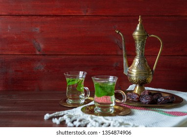 Iftar and Suhoor Ramadan concept ,mentha tea on glass cups and dates on wooden background with an old tea pot