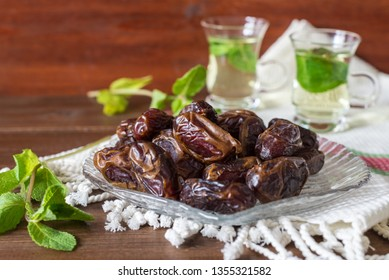 Iftar or Suhoor snack close up of dates on glass plate with mentha tea on background , Ramadan concept