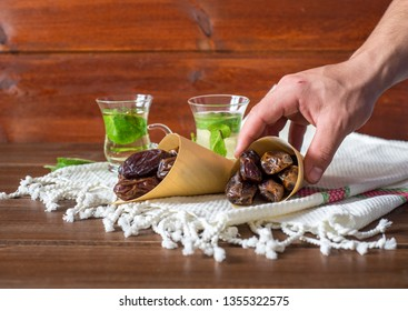 Iftar or Suhoor snack , hand of a man with a conus of dates with mentha tea on background , Ramadan concept