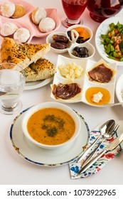 Iftar table of Ramadan with symbolic foods.Soup (Ezo gelin),date,black olives,dry-aged beef and ramadan bread (pide) on the white table.Vertical shot,top view.