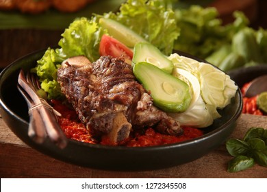 Iga Penyet. Javanese dish of fried smashed beef ribs served on red chili paste with fresh vegetables aside.