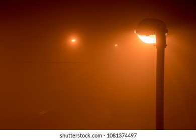 ight view on the street with a yellow street light on the right side of the frame surrounded by the fog from the pollution of the air