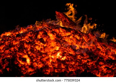 Ignite the fire. Warming up the cold winter nights. A macro shot of firewood and hot, glowing coal. Burning branches and wood. Flames in the fireplace, cozy home, warmth, love, romantic