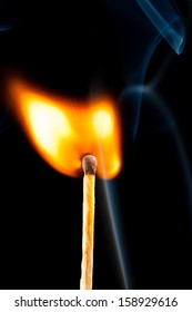 igniting match with smoke, black background