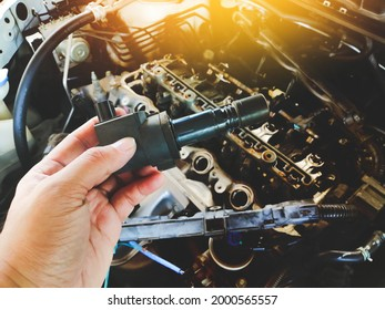 Ignition coil for spark plug of the car ignition system in the mechanic hand with a car engine blurred background in the repair garage