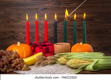 ignition of Kwanzaa traditional candles, festival concept with gift box, pumpkins, ears of wheat, grapes, corns, banana, bowl and fruits on wooden background, close up