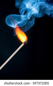 Ignition match with smoke closeup on black background
