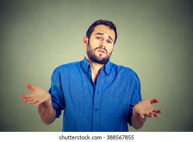 Ignorance and arrogance. Closeup portrait young man shrugging shoulders who cares so what I don't know gesture isolated on gray wall background. Human body language. Whatever attitude reaction