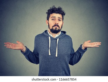 Ignorance and arrogance. Portrait of a young man shrugging shoulders feeling clueless isolated on gray background. Whatever attitude reaction