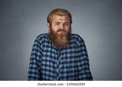 Ignorance and arrogance. Young bearded man shrugging shoulders who cares so what. Hipster male with beard in blue plaid checkered shirt  Isolated gray grey studio Background. Negative face expression.