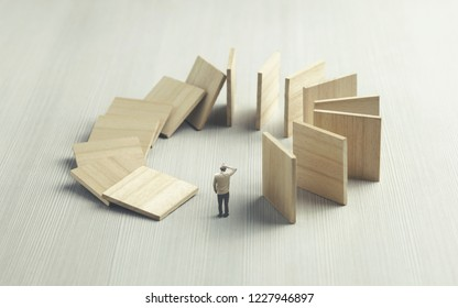 ignorant man watching domino collapsing on him, surreal concept