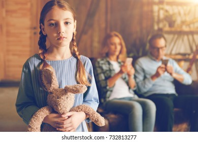 Ignored upset child posing with her bunny toy