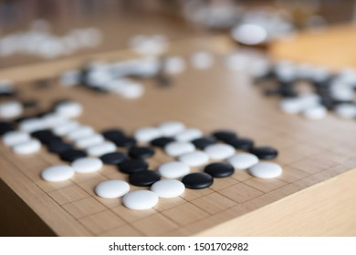 igo, baduk or weiqi stone on wooden board