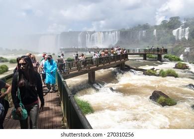IGUACU, BRAZIL - FEB 5, 2015: Tourists admire Iguacu (Iguazu) falls on a border of Brazil and Argentina
