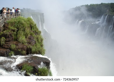 IGUASSU FALLS, ARGENTINA - OCTOBER 19, 2006. People looking out over Iguassu Falls on the border of Brazil and Argentina. Argentinian side. Dozens of swiftlets can be seen soaring through the mist.