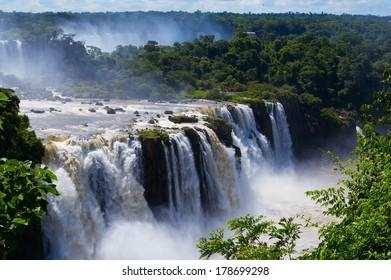 Iguazu Falls or Iguassu Falls in Brazil. Beautiful Cascade of waterfalls with clouds and jungle