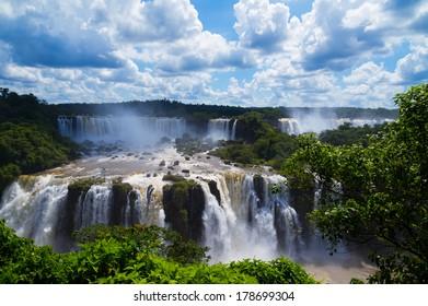 Iguazu Falls or Iguassu Falls in Brazil. Beautiful Cascade of waterfalls with cloudscape